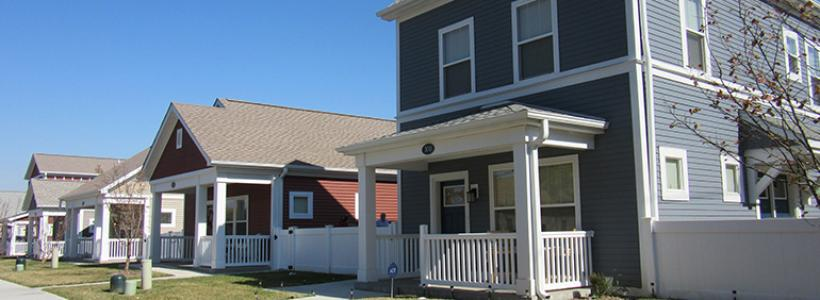 A two story standalone gray house with a white fence and roof above the front porch and white windows, next to a one story red house with similar accents.